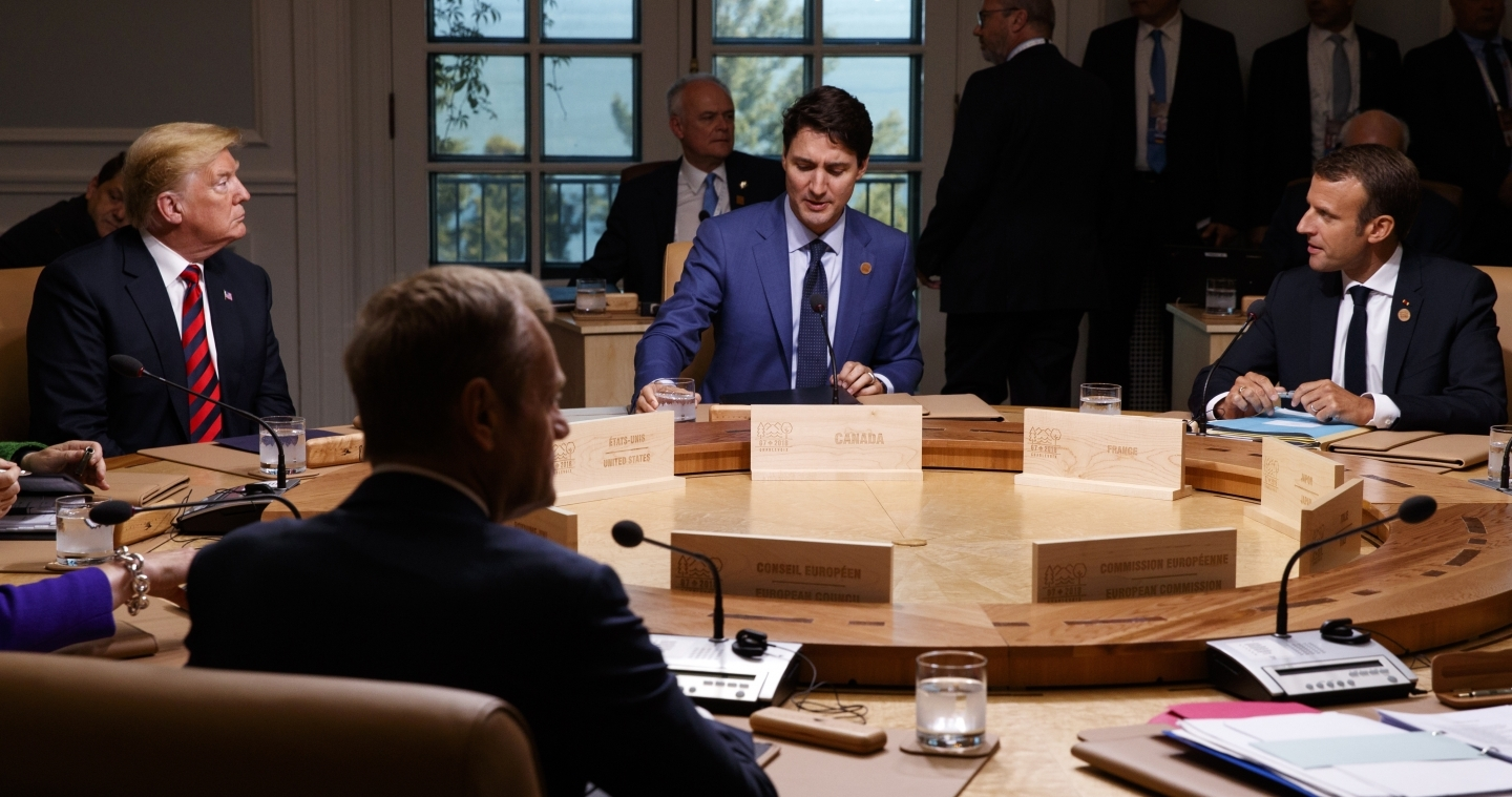 President Donald Trump talks with Canadian Prime Minister Justin Trudeau and French President Emmanuel Macron during a G7 Summit working session on June 8, 2018. (AP Photo/Evan Vucci)