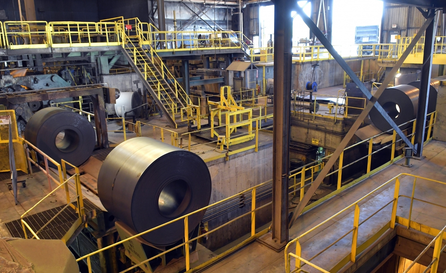New rolls of sheet steel exit the spooling machine, and head off to cool down at the NUCOR Steel Gallatin plant on July 25, 2018, in Ghent, Kentucky. (AP Photo/Timothy D. Easley)