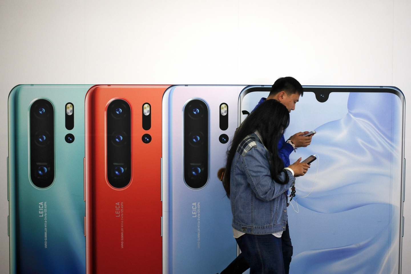 Two people browse their smartphones as they walk by a Huawei P30 smartphone advertisement in Beijing on May 13, 2019. (AP Photo/Andy Wong)