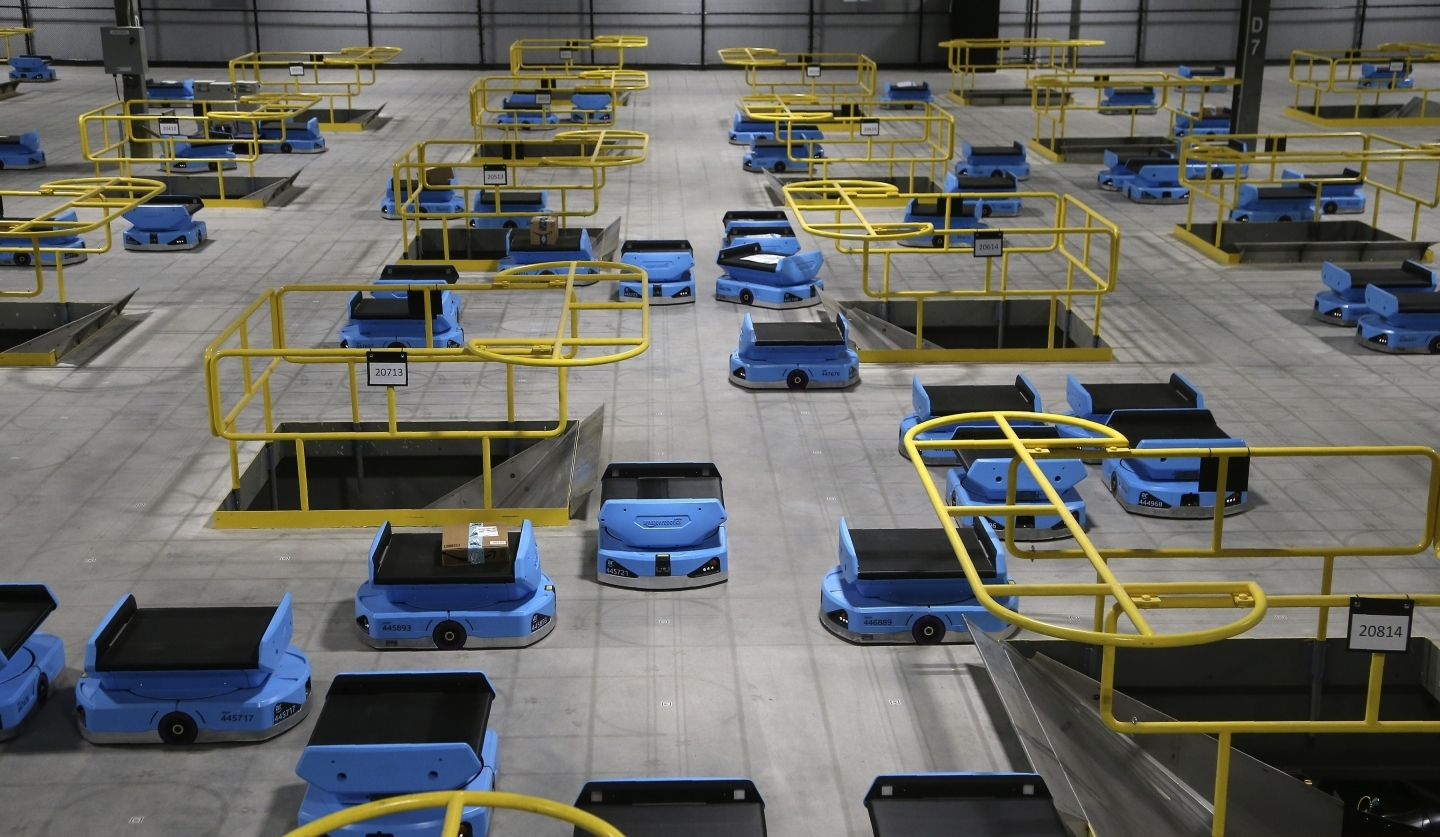 Dozens of Amazon robots transport packages from workers to chutes that are organized by zip code, at an Amazon warehouse facility in Goodyear, Arizona. (AP Photo/Ross D. Franklin)