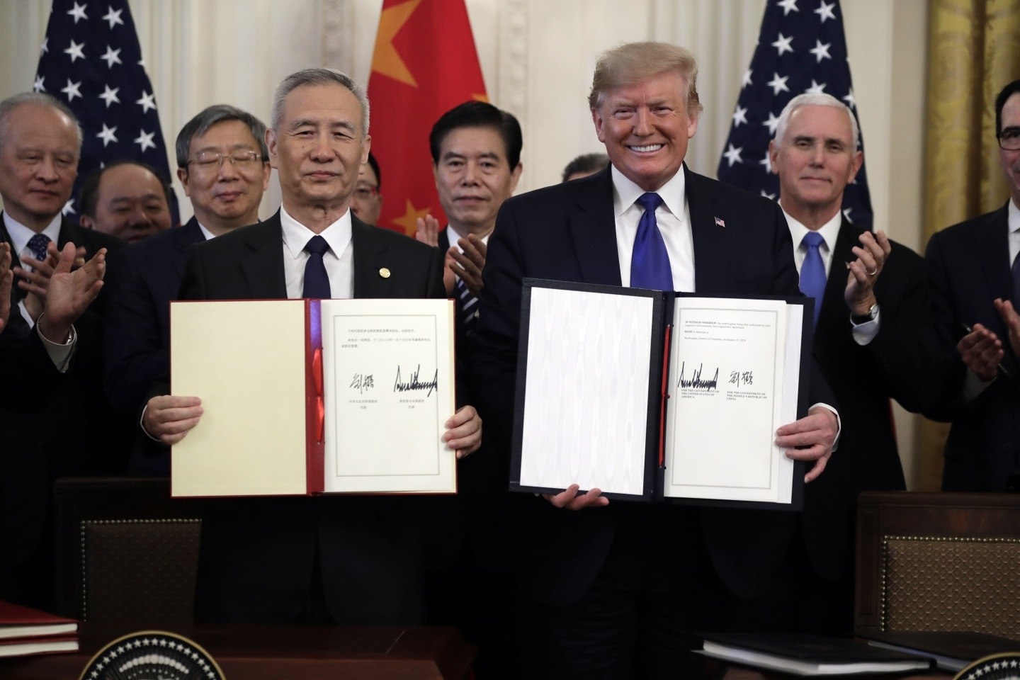 U.S. President Donald Trump, right, signs a trade agreement with Chinese Vice Premier Liu He. (AP Photo/Evan Vucci)