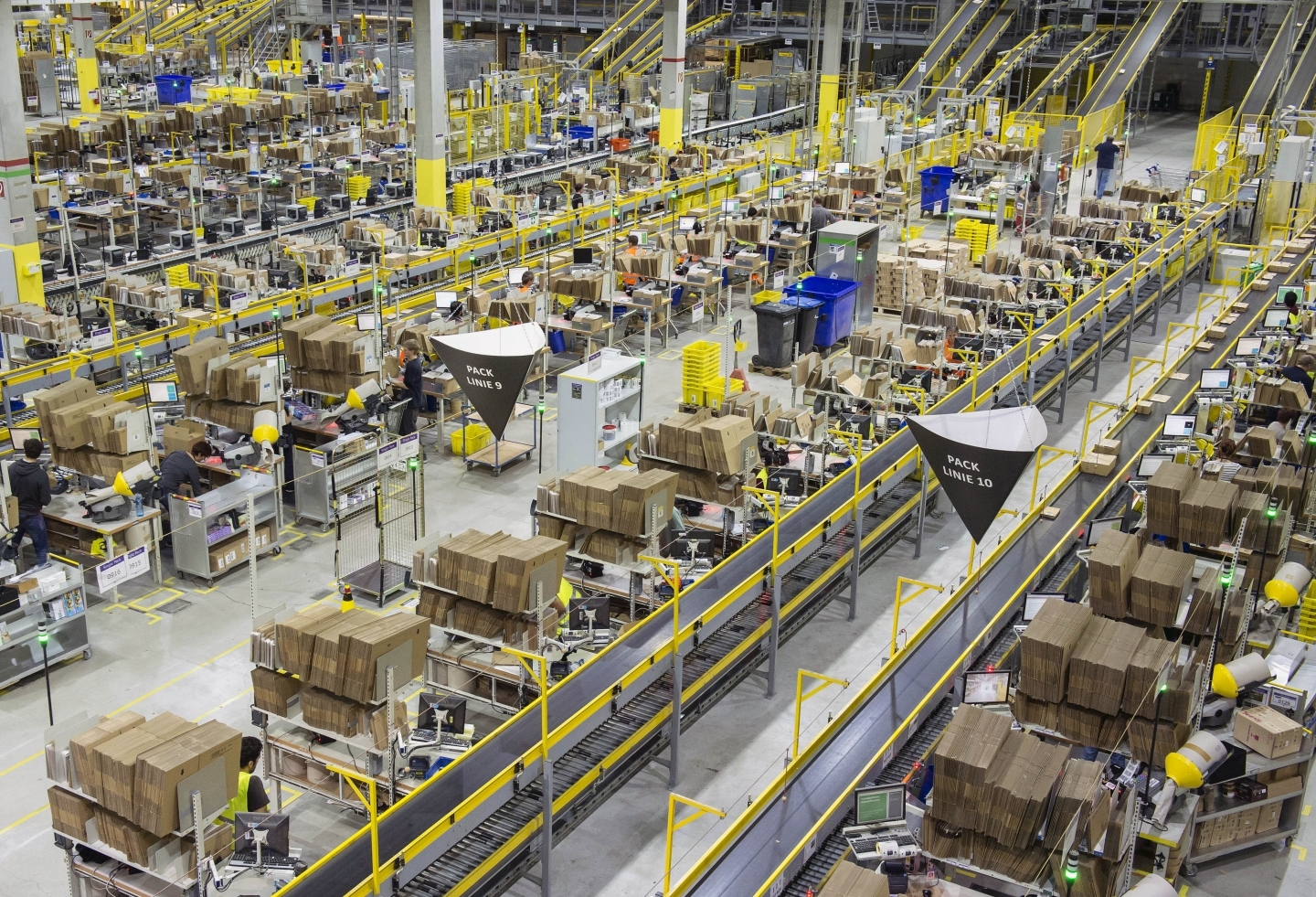 Artificial intelligence and people work side by side in an Amazon distribution centre. (AP Photo/Jens Meyer)