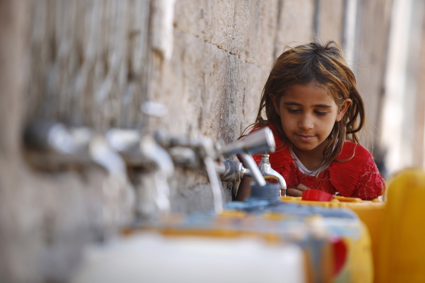 A girl fills a container with water from a public tap in the old city of Sanaa, Yemen (AP Photo/Hani Mohammed)