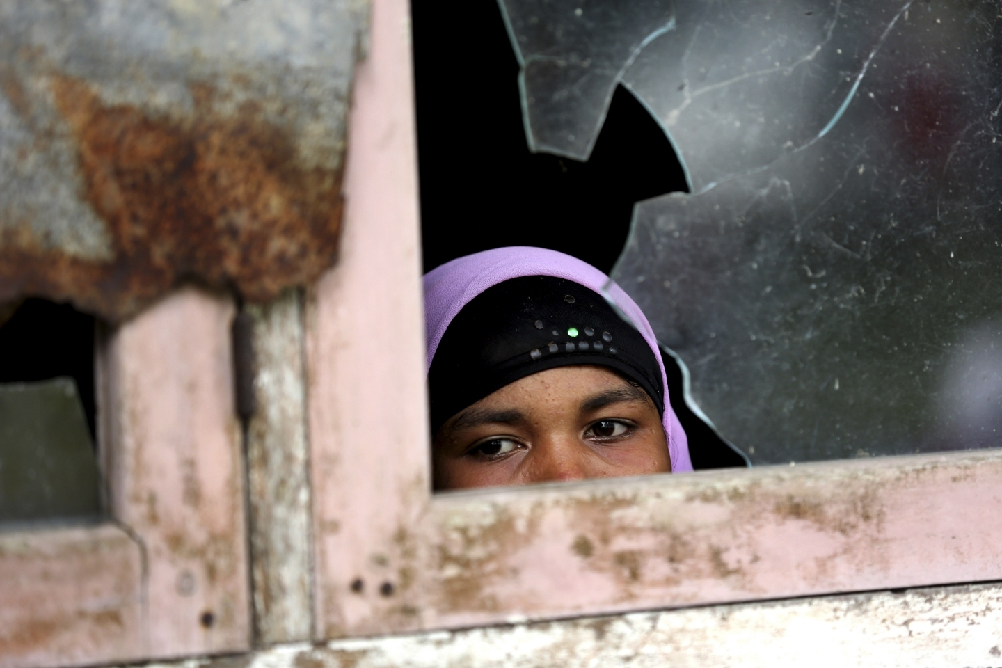 A woman peers out from a temporary shelter housing ethnic Rohingya displaced by internal conflict in Myanmar (AP Photo/Tatan Syuflana)