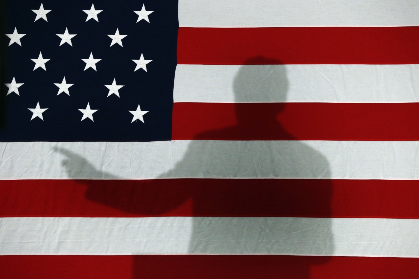 Former President Bill Clinton casts a shadow on an American flag during a 2016 campaign stop (AP Photo/Paul Sancya)