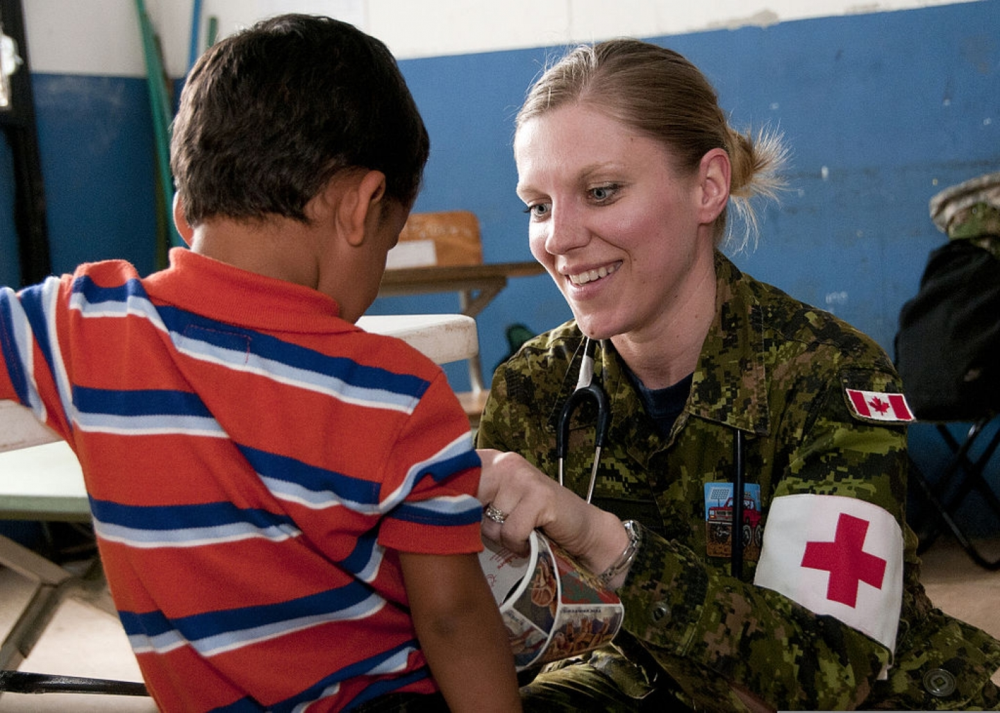 """Canadian Forces Capt. Karoline Martin, a nurse with the Canadian Forces Health Services Center, gives a child a sticker after an examination during a medical clinic April 15, 2013, in Caluco, El Salvador"". Photo by TSgt Mark Wyatt [Public domain], via Wikimedia Commons"