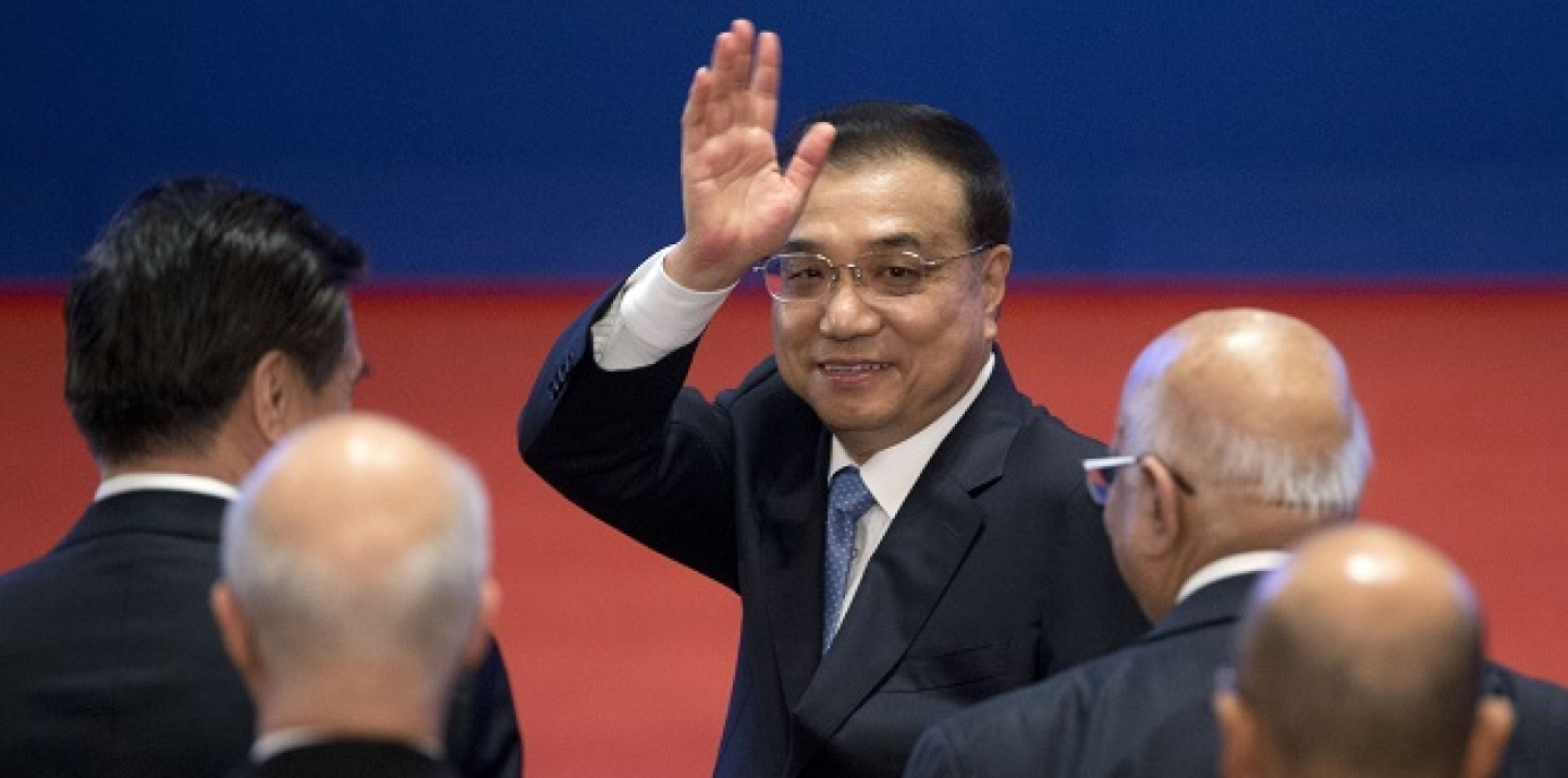 Chinese Premier Li Keqiang, center, waves as he leaves the Inaugural Meeting of the Board of Governors of the Asian Infrastructure Investment Bank (AIIB) in Beijing, China, Saturday, Jan. 16, 2016. (AP Photo/Mark Schiefelbein, Pool)