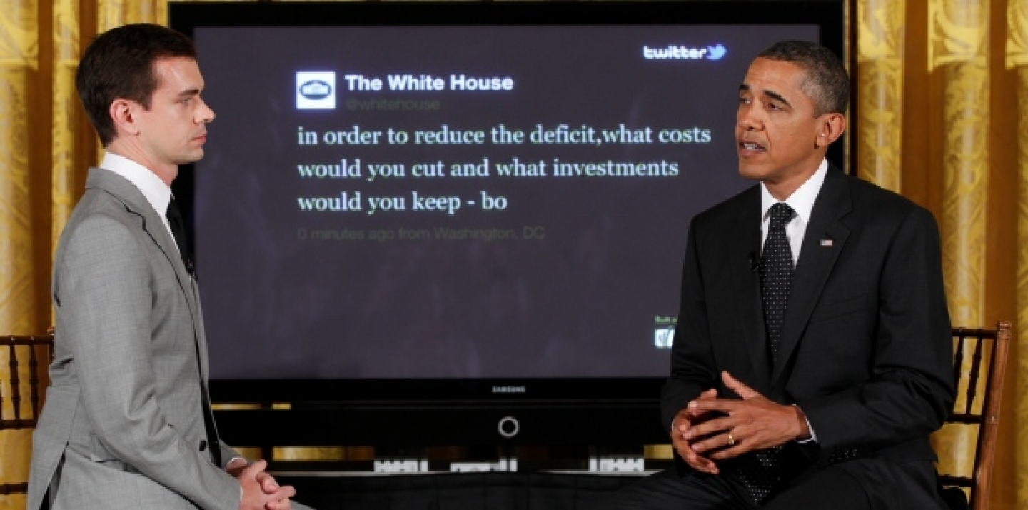 "President Barack Obama sits with Twitter co-founder and Executive Chairman Jack Dorsey in front of a screen displaying the question he tweeted during a ""Twitter Town Hall"" (AP Photo/Charles Dharapak)."