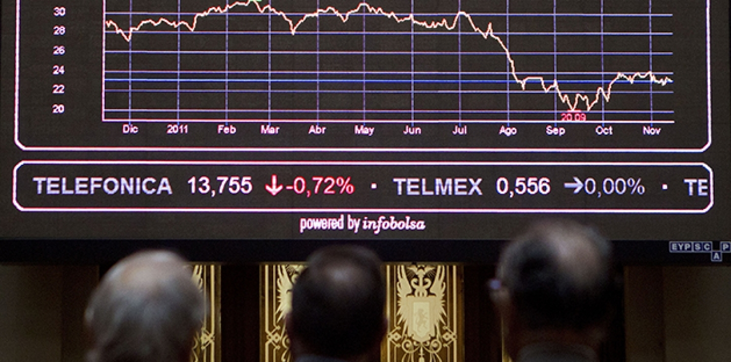 Brokers look at the main screen at the Stock Exchange in Madrid. (AP Photo/Paul White)