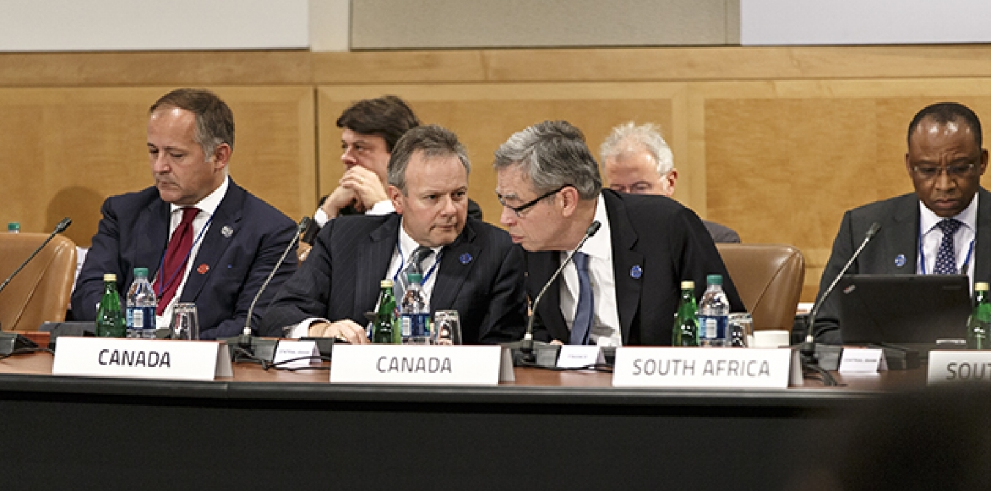 Canada's Minister of Finance Joe Oliver, center right, leans in to speak with Stephen Poloz, governor of the Bank of Canada, center left, as the Group of Twenty nations gather at the International Monetary Fund and World Bank meetings in Washington. (AP Photo/J. Scott Applewhite)