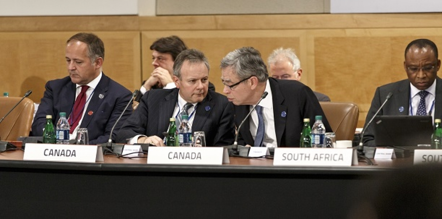 Canada's former finance minister, Joe Oliver, center right, leans in to speak with Stephen Poloz, governor of the Bank of Canada, center left, as the Group of Twenty nations gather at the International Monetary Fund and World Bank meetings in Washington, Friday, Oct. 10, 2014.(AP Photo/J. Scott Applewhite)