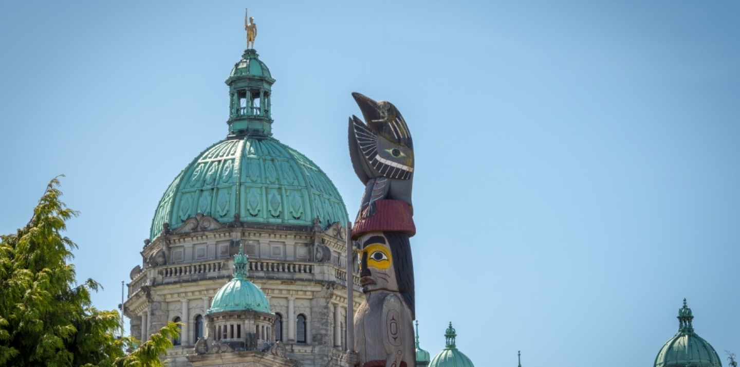 The Provincial Capital Legislative Parliament Building behind a First Nations totem pole in Victoria, British Columbia. (Shutterstock)
