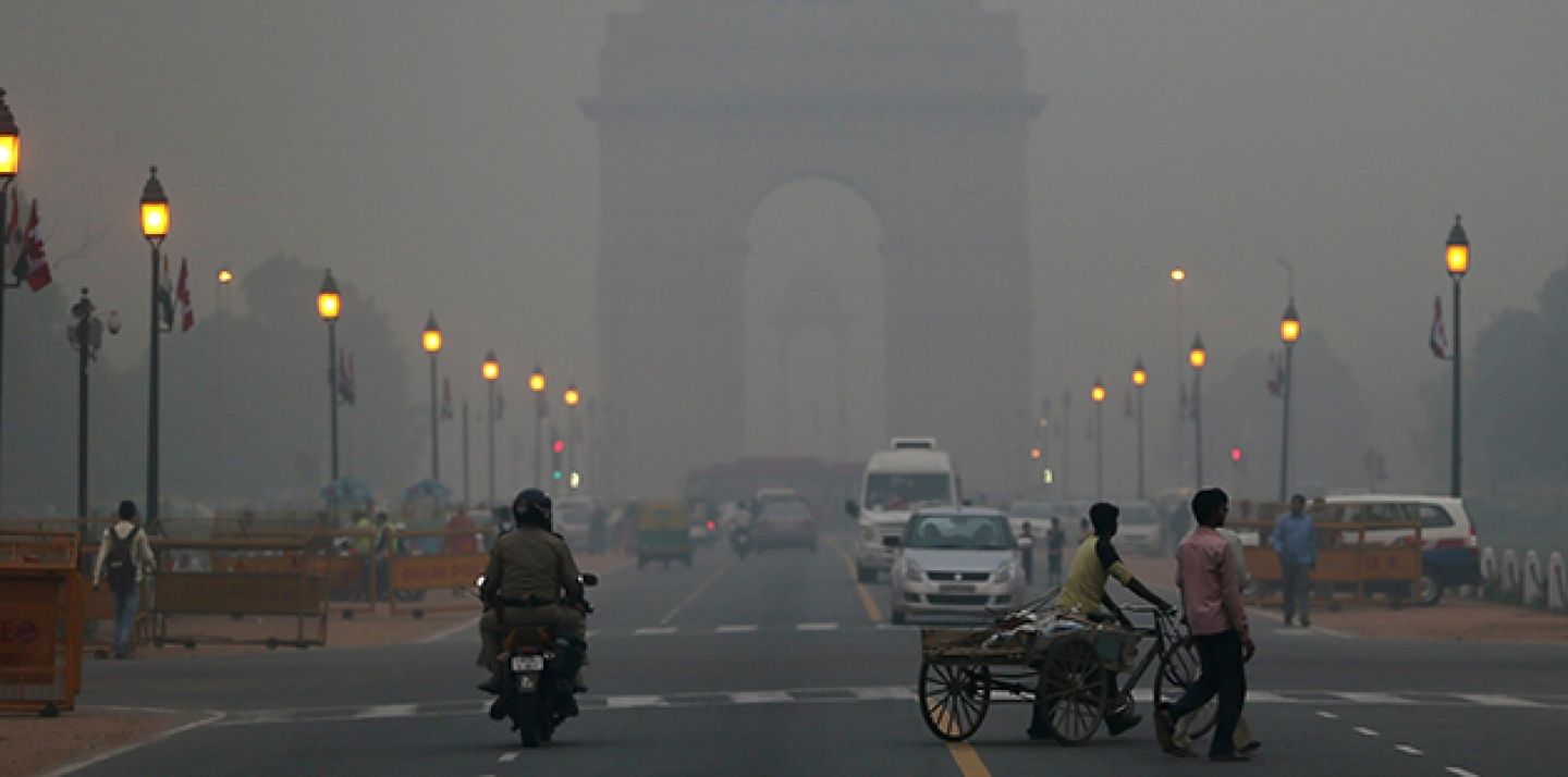 Traffic moves in front of the landmark India Gate monument enveloped by a blanket of smog. (AP Photo/ Manish Swarup)