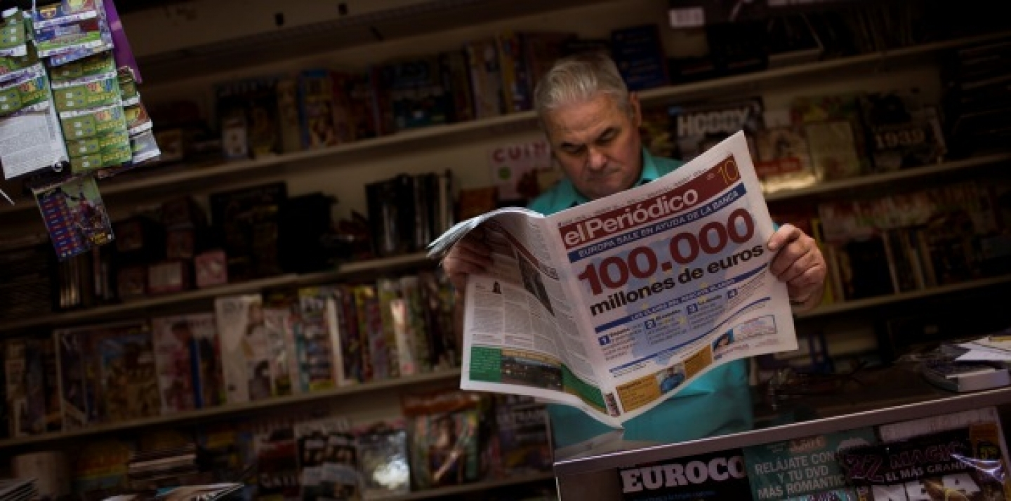 A man reads a newspaper announcing a bailout of up to euro 100 billion ($125 billion) to rescue failing banks, in a bookstore in Barcelona, Spain (AP Photo/Emilio Morenatti).