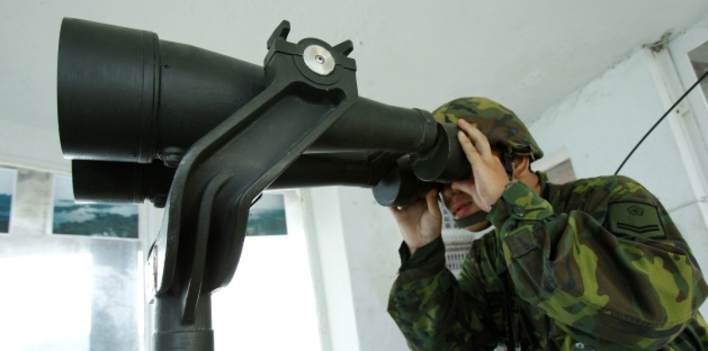 A Taiwanese soldier peers through binoculars towards China just 1.8 kilometers from his frontline pillbox. (AP Photo/Wally Santana)
