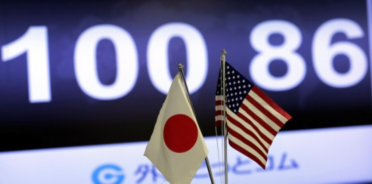 The exchange rate of the U.S. dollar against Japanese yen is shown behind both countries' flags at an exchange in Tokyo, Friday, May 10, 2013. The yen broke the the psychologically important 100 yen to the dollar mark. (AP Photo/Itsuo Inouye)