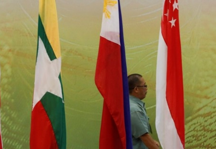 A staff walks behind of ASEAN country flags at new prime minister's office in Bandar Seri Begawan, Brunei, Tuesday, April 23, 2013. (AP Photo/Vincent Thian)