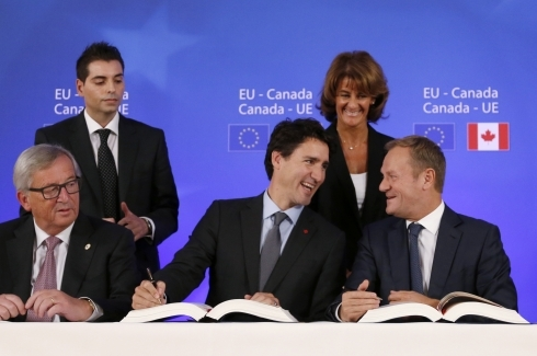 Canadian Prime Minister Justin Trudeau, center front, sits with European Commission President Jean-Claude Juncker, left, and European Council President Donald Tusk, right, as they sign the Comprehensive Economic and Trade Agreement (CETA) during an EU-Canada summit at the European Council building in Brussels (Francois Lenoir/Pool Photo via AP)