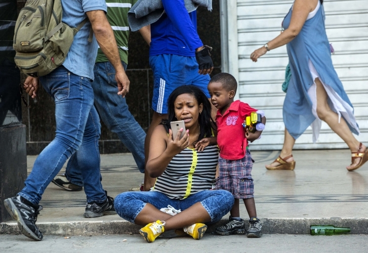 A woman with her child uses a public wifi hotspot in Havana, Cuba (AP Photo/Desmond Boylan)