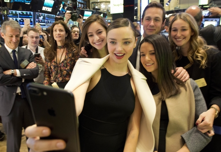 Model Miranda Kerr takes selfie during NYSE opening bell to mark Snap IPO. Kerr is engaged to Snap CEO Evan Spiegel. (AP Photo/Mark Lennihan)