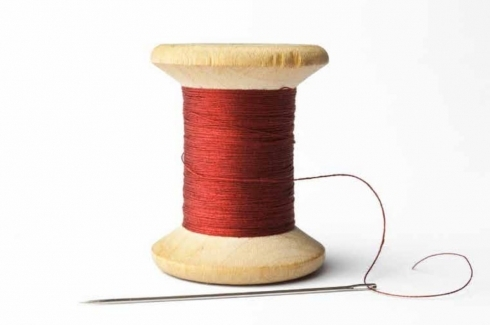 "A spool of red thread, the cover Image of CIGI Paper No. 213 ""Curbing Cultural Appropriation in the Fashion Industry"" by Brigitte Vézina"