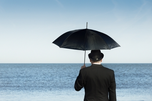 Man with umbrella standing by ocean