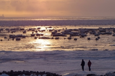 Wanderers on the ice-covered wadden sea in Büsum at low tide - the structure visible on the horizon is the North Sea offshore oil rig Mittelplate - about 7 km (4.3 mi) in the distance. (Flickr Photo / BlueRidgeKitties under creative commons)