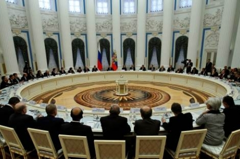 Russian President Vladimir Putin, center between two flags, speaks to financial ministers and heads of central banks of the G20 group of nations. (AP Photo/Alexander Zemlianichenko)