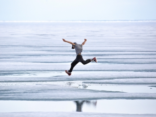 A boy hops across melting summer sea ice just outside of Cambridge Bay, Nunavut. (Zachary Prong/Arctic Research Foundation)
