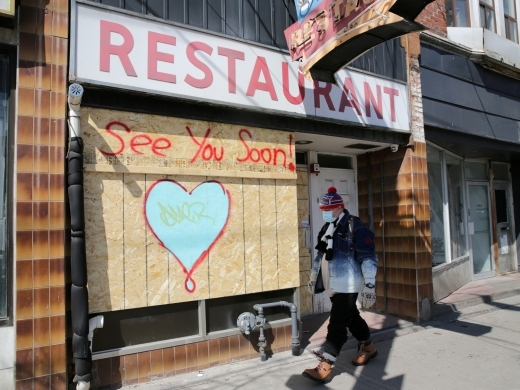 A man passes a boarded up restaurant during the global outbreak of the coronavirus disease (COVID-19) in Toronto, Canada on April 6, 2020. (Reuters/Chris Helgren/File Photo)