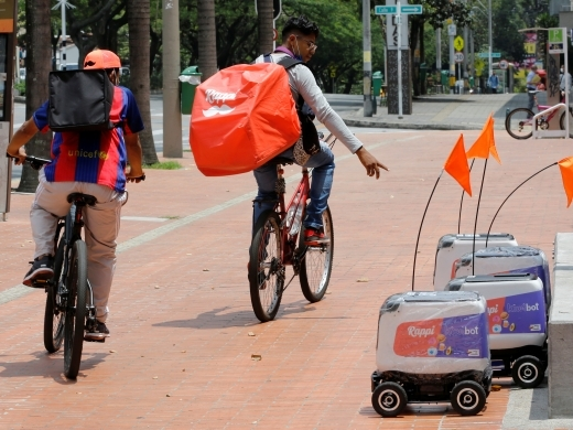Delivery workers cycle past delivery robots from the Colombian company Rappi, in Medellin, April 13, 2021. (REUTERS/David Estrada)