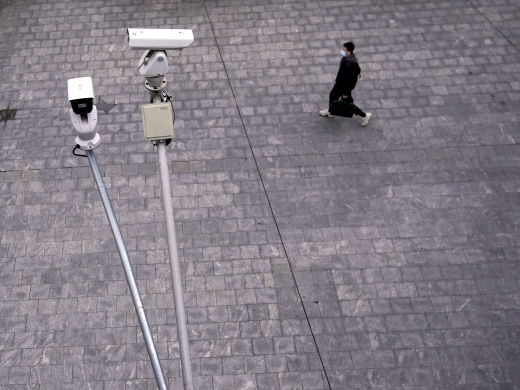 A man wearing a protective mask walks under surveillance cameras on February 28, 2020. (Reuters/Aly Song/File Photo)