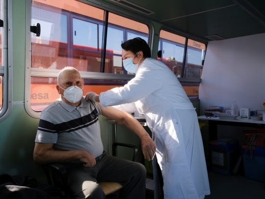 "A Venice resident receives a coronavirus disease vaccine on board a traditional ""vaporetto,"" a ferry normally used for public transportation in Venice, Italy on April 5, 2021. (Reuters/Manuel Silvestri)"