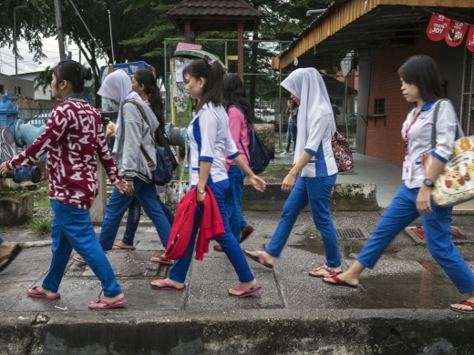 A group of young women migrant workers make their way to a nearby factory facility where they work in Petaling Jaya, Malaysia. (UN Women/Staton Winter)