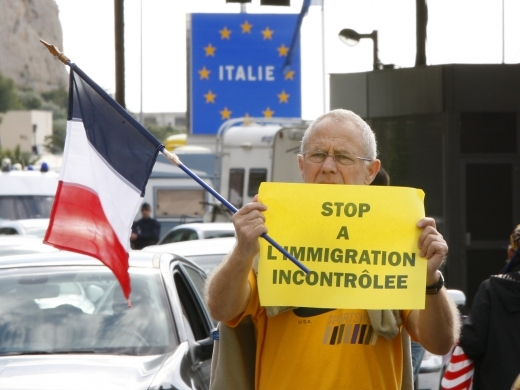 An unidentified French far-right National Front party demonstrator holds an anti-immigration sign (AP Photo/Antonio Calanni)