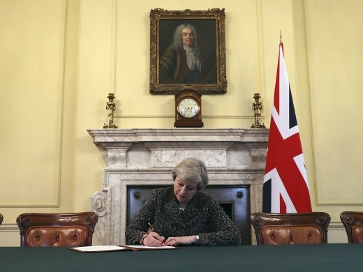 Britain's Prime Minister Theresa May, sitting below a painting of Britain's first Prime Minister Robert Walpole, signs the official letter to European Council President Donald Tusk, in 10 Downing Street, London, Tuesday March 28, 2017, invoking Article 50 of the bloc's key treaty, the formal start of exit negotiations. (Pool Photo via AP/Christopher Furlong)