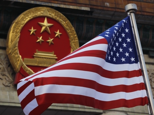 An American flag is flown next to the Chinese national emblem during a welcome ceremony for visiting US President Donald Trump outside the Great Hall of the People in Beijing, Thursday, Nov. 9, 2017. (AP Photo/Andy Wong)