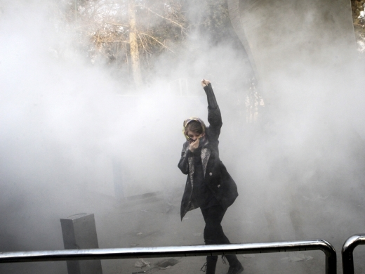 A protestor runs from a smoke grenade thrown by anti riot police during a December 30 rally against the Iranian government. (AP Photo)