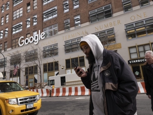 A man using a mobile phone walks past Google offices in New York. (AP Photo/Mark Lennihan)