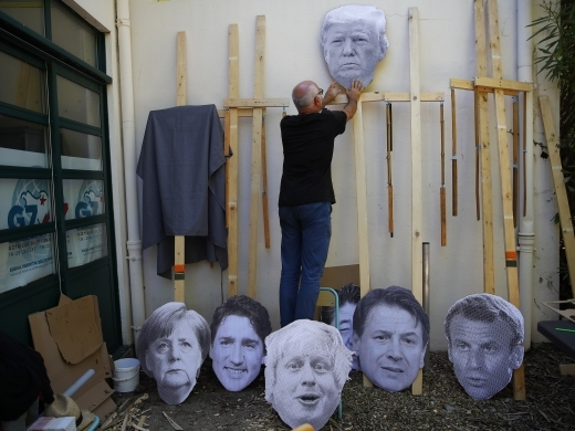 A man fixes an image of President Donald Trump to a wooden pole as he prepares for an anti-G7 demonstration at a camp near Hendaye, France. (AP Photo/Francois Mori)