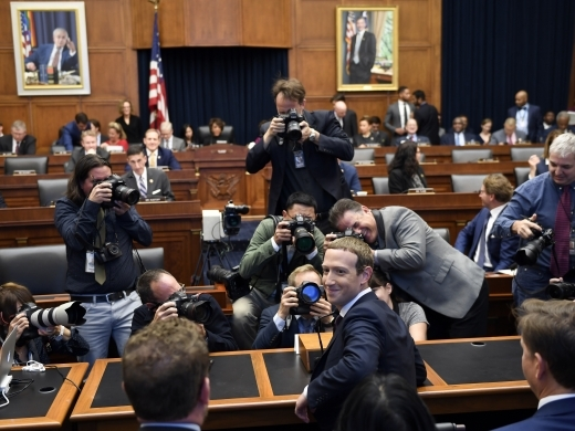 Facebook Chief Executive Officer Mark Zuckerberg turns back and smiles after arriving for a hearing before the House Financial Services Committee on Capitol Hill on October 23, 2019. (AP Photo/Susan Walsh)