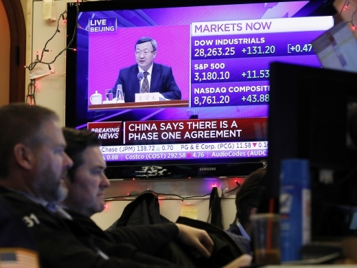A television screen on the floor of the New York Stock Exchange, Friday, Dec. 13, 2019. (AP Photo/Richard Drew)