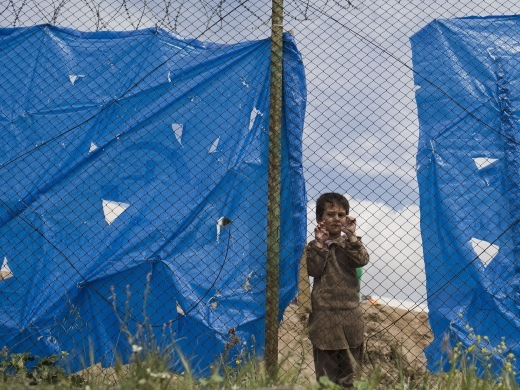 Omar, a five-year-old Afghan boy looks out behind a wire fence of a refugee camp in the western Athens' suburb of Schisto on March 28, 2016. (AP Photo/Petros Giannakouris)