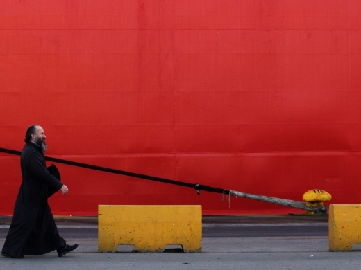 A Greek orthodox priest passes a docked ship during a general strike against austerity (AP Photo/Petros Giannakouris)