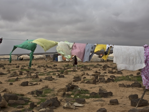 A Syrian refugee woman walks at an informal tented settlement near the Syrian border on the outskirts of Mafraq, Jordan on January 23, 2016. (AP Photo/Muhammed Muheisen)
