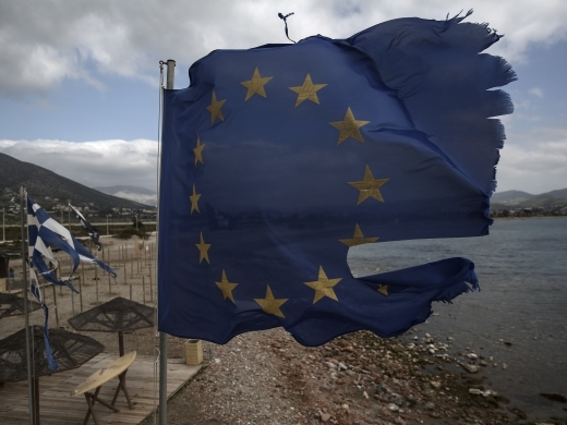 EU and Greek flags fly in tatters | Photo by Yorgos Karahalis