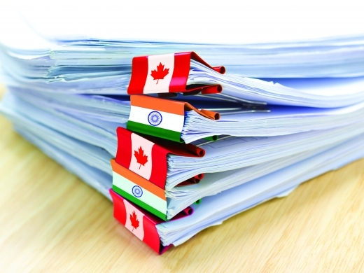 Stack of individual documents bound with clips displaying flags of India and Canada