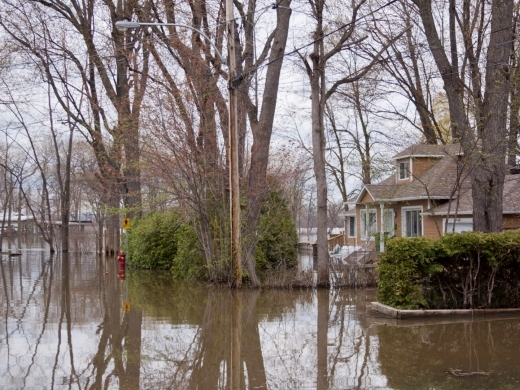 Landscape view of flood waters rising over a paved road in front of properties with trees, foliage, in the West Island of Montreal, Quebec