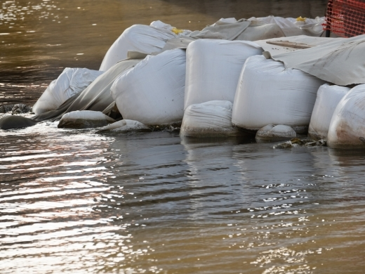 sandbags at flooded river's edge