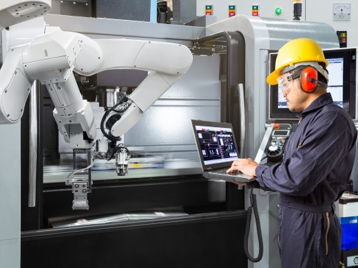 Maintenance engineer using laptop computer control automatic robotic hand with CNC machine in smart factory. (Shutterstock)